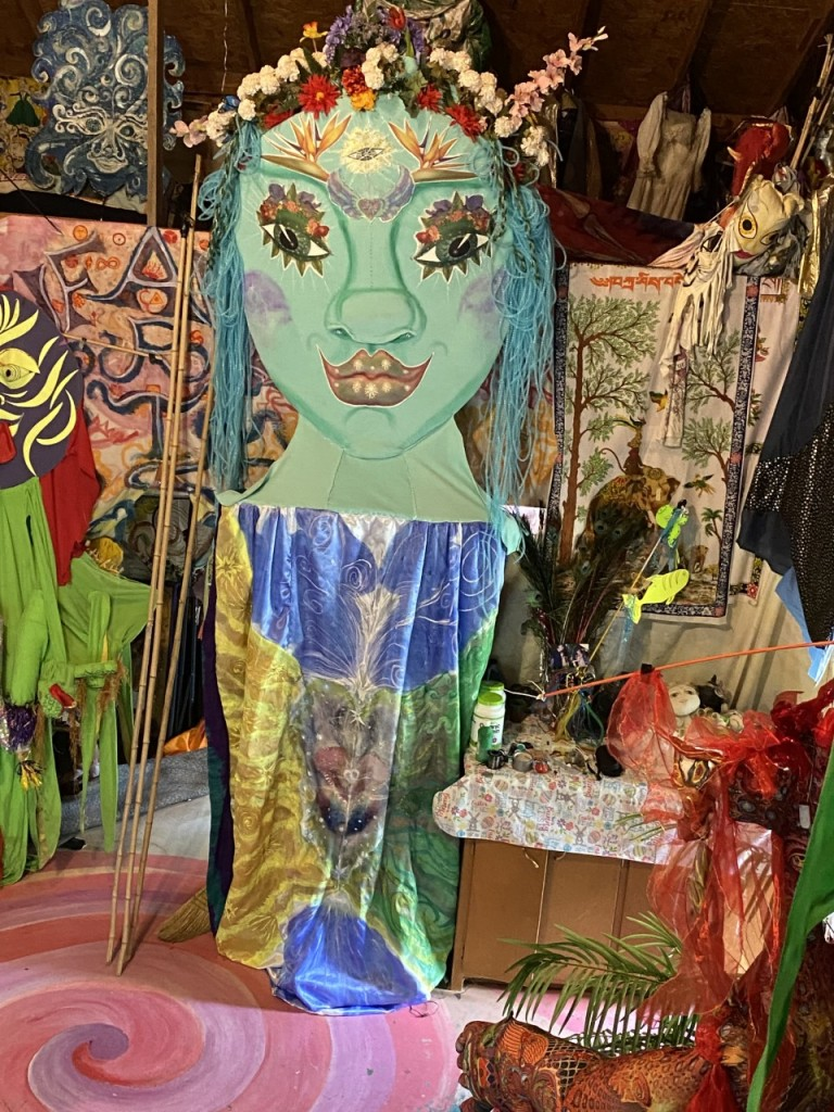 A colorful jumble of props from Kids Camp performances, including a large green puppet.